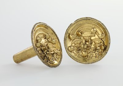Ear studs, pair, of hammered and engraved gold. The concave disks iwth beaded edges are decorated with an applied motif bearing four figures. Above, a demi-god with elaborate aureole headdress riding on a bar borne by other three figures. In one hand he holds a beaker-cup; in the other a bag adorned with loose bangles. Two of the lower figures wear modified aureole headdresses and carry beakers. All are half human, half beast. The bar on which the demi-god rides is finished at the ends with demon heads. Loose bangles are variously applied in the design. The tubes of the ear studs are decorated with engraved bands of cats and birds, and soldered to the backs of discs.