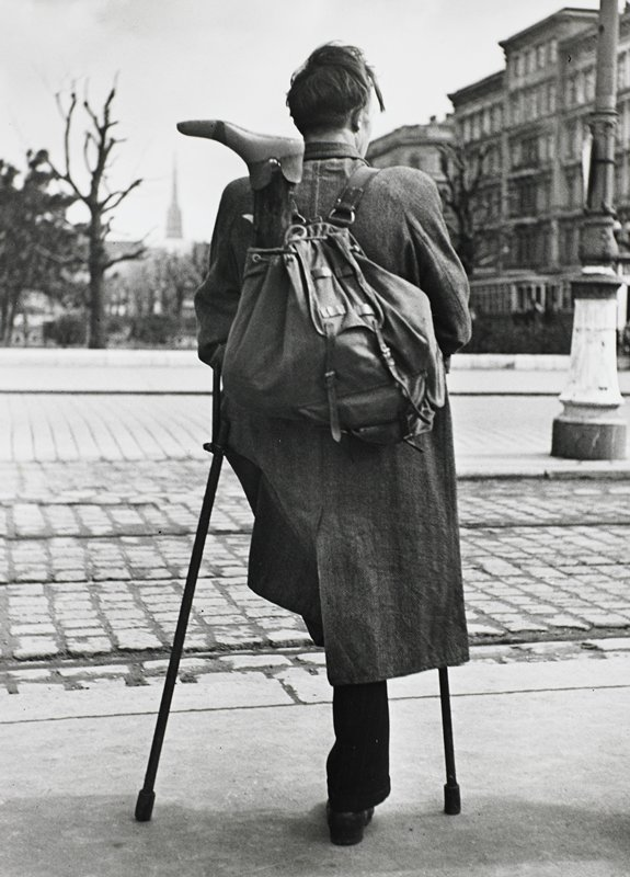 standing man with one leg, on crutches, seen from back; man has his artificial leg in a knapsack on his back; city view in background