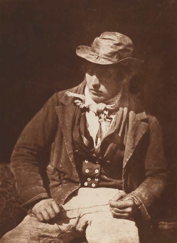 seated man wearing a hat, short jacket, vest, and bandana, looking down toward lower left corner; sepia toned