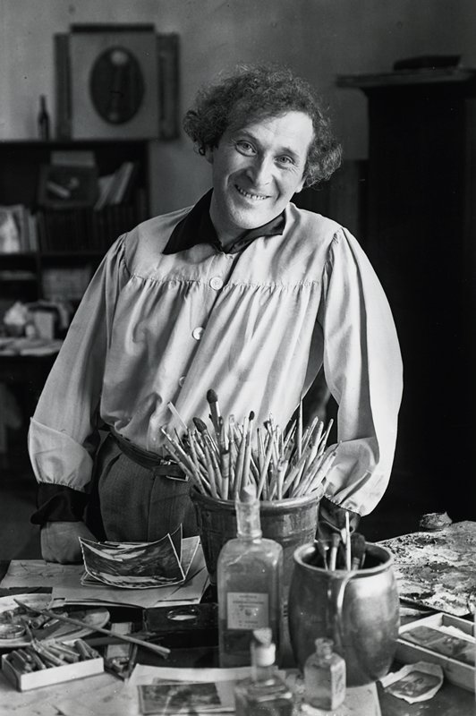 smiling man standing behind a table with large pots of brushes, paints, papers, and a palette; man has curly hair and wears a smock with gathered sleeves and yoke