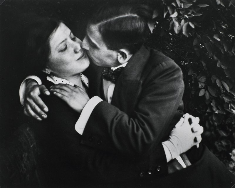 man and woman with arms around each other, about to kiss; man wears bowtie and jacket; woman wears gloves; leaves in background