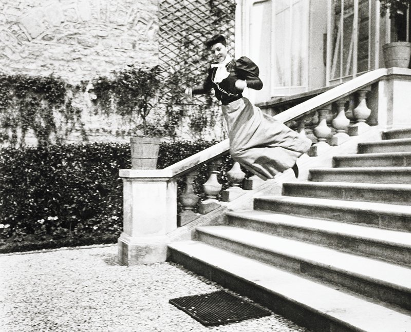 woman leaping over steps; staircase outside building; potted plants at top and bottom of railing; mat at bottom of steps