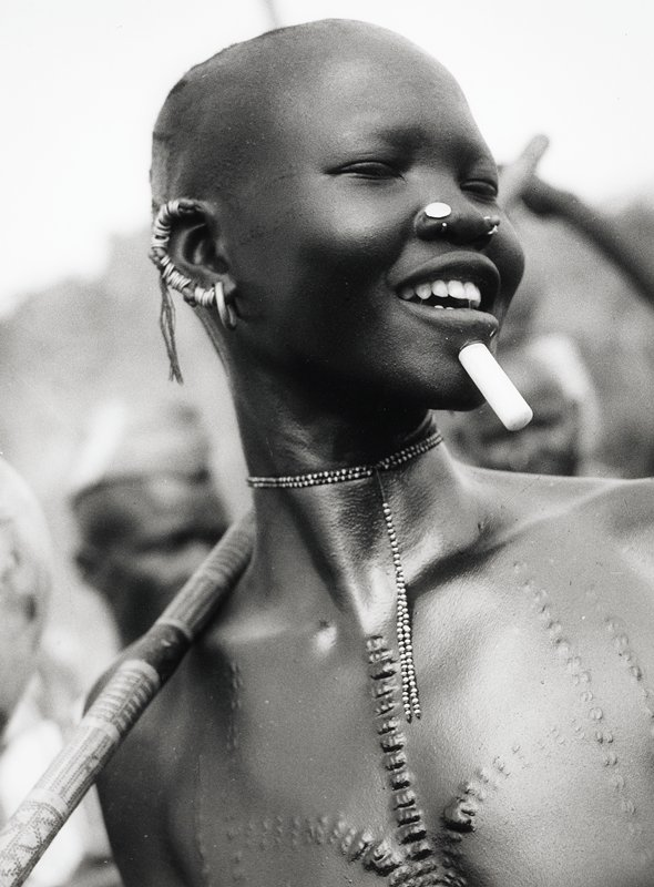 portrait bust of black girl; scars on chest; small rings cover proper right ear lobe; one larger ring at bottom; white rod below lip; decorative nose ring and round disk; bead necklace around neck has two strands of small beads