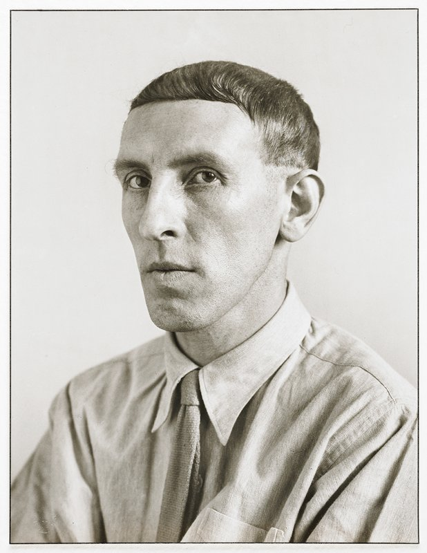portrait of man with pointed chin and flat, short hair, combed to the left; man wears shirt and tie