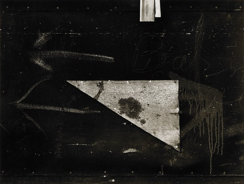 nearly abstract image of dark nailed, painted panels with two chalk arrows at left and cursive writing at right; triangular nailed element at center