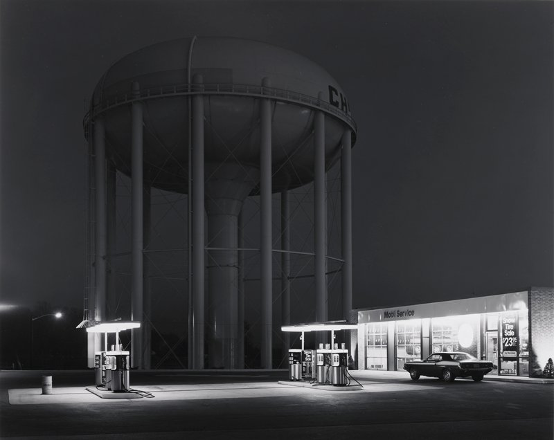 Mobil gas station at night; two service islands and building lighted; car parked in front of station; huge water tower not illuminated in background