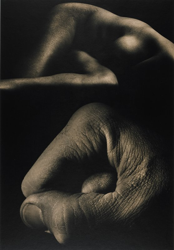 lower half of image shows a close-up of a clenched fist, thumb and forefinger; upper half of image nude female torso