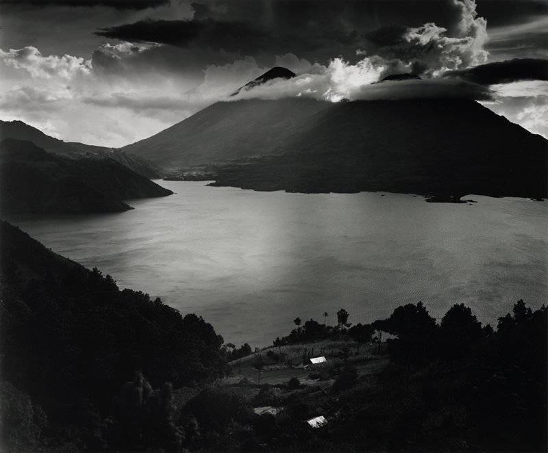 lake surrounded by hills, buildings in foreground; low clouds over hills in background