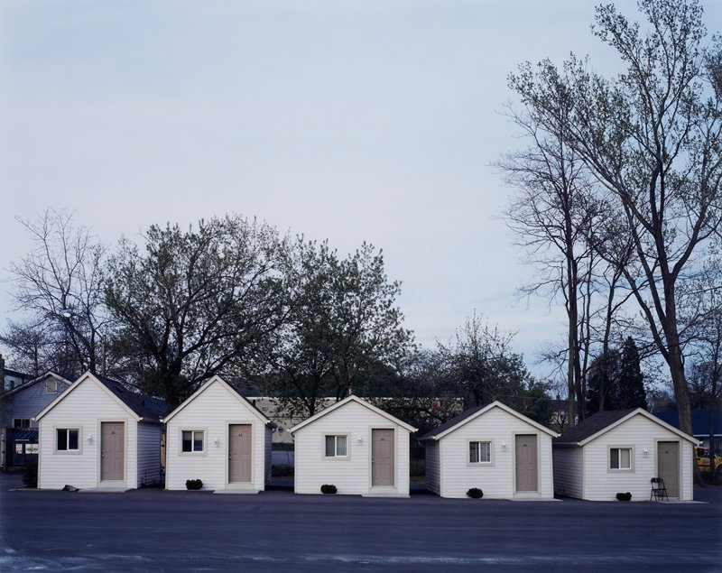 five very small light tan cottages with light brown doors; concrete surrounds cottages; row of trees behind