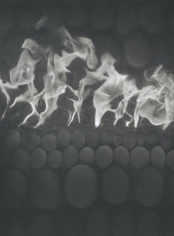 abstracted image; horizontal rows of different sized round elements at top and bottom; flames at center