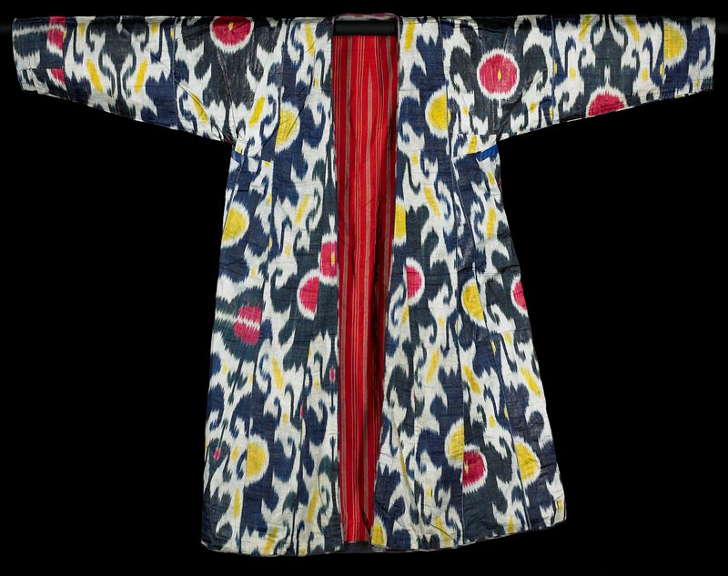 long coat with long sleeves and short side vents; blue, white, yellow, green and red ikat; predominately lined in red fabric printed with grey fancy stripe design