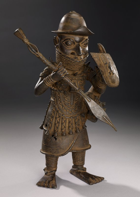 standing figure wearing a hat with turned-up brim in front, neck and mouth covering, armor-like tunic and anklets; figure holds spear in PR hand and removable shield in PL hand; bare feet; bell-like pendant on element at PL hip