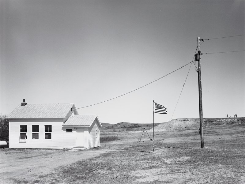small white schoolhouse; flagpole and flag, swing set; figures on hill top right side