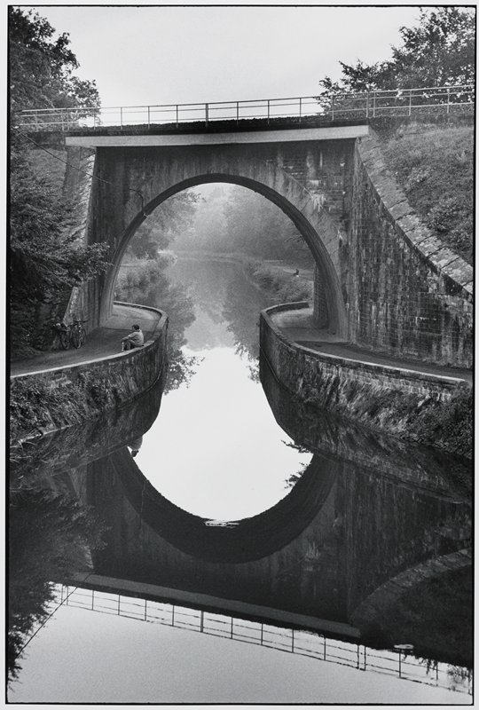 railway bridge over a canal reflected in canal's still water; figure seated on canal wall at left watching a second figure adjusting one of two bicycles leaning against bridge wall
