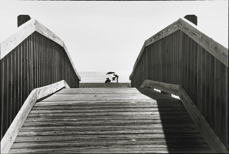 wood bridge with hump leading to beach; two figures - one seated in beach chair, one standing beneath an umbrella beyond end of bridge