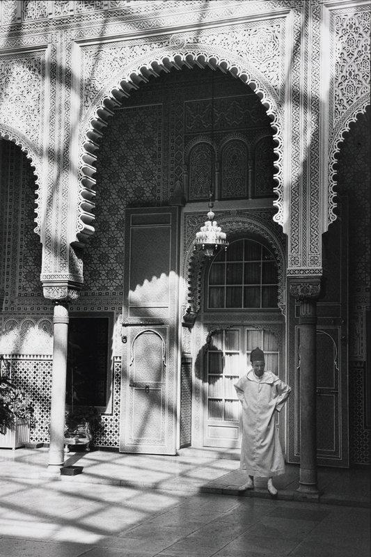 man standing below decorative archway in front of door