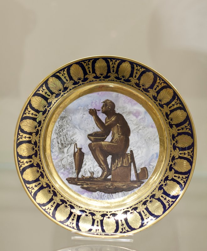 Plate, ceramic-porcelain, seated figure eating out of a bowl with Greek vase at his feet, French, XIXc cat. card dims H 1-1/4 x diam 9-1/8' Holiday Traditions, French Room. Part of a dessert service that has been attributed to Pièrre André Le Guay (active 1773-1817), and Joseph Leopold Weydinger (active 1778-1829)