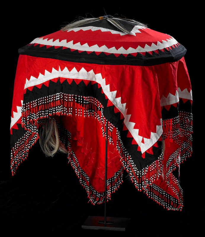 saucer-shaped, with cloth hanging down around edges; beaded chin strap with cross designs; tassels on crown and chin strap with grey and brown hair and multicolored beads; large black square with white cross and zigzag edging on crown; red, white and black fabrics and beads on fringe and chin strap