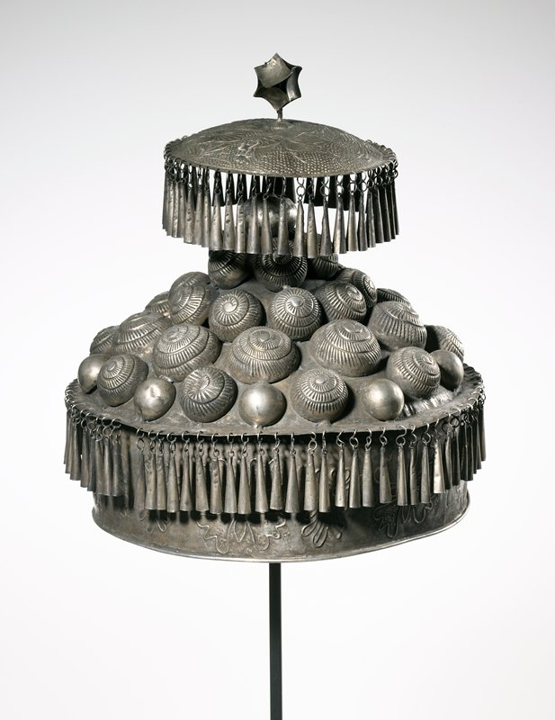 conical hat with chime-like tassels; hat has a second flat, circular piece that sits above the main body of the hat, this circle also has chime-like tassels; circle has decorative tassel made from nine curved metal squares soldered into a sphere; main body of hat is covered with half circles in relief; flat band on side of hat has relief of leaves on it; circle on top has fish design with tiny-dot background