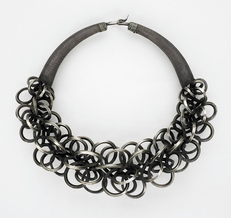 single ring with center of curled, twisted, thick square wire which creates large spirals; ends wrapped in very thin braided wire; closure: large wire loop and hook