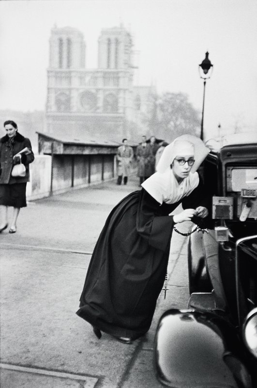young nun, wearing glasses, leaning on a car; other figures in background