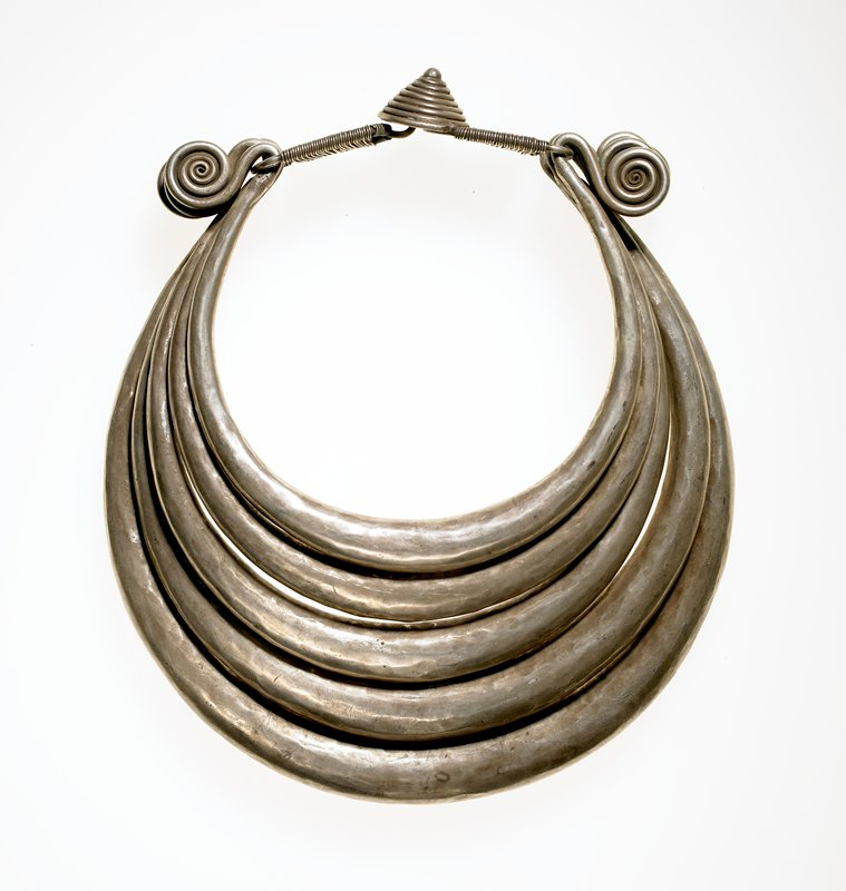 five wide undecorated strands each ending in a spiral hook attached to closure rings; closure in two pieces joined at center by hook and eye under beehive-like motif; closure rings are wire wrapped