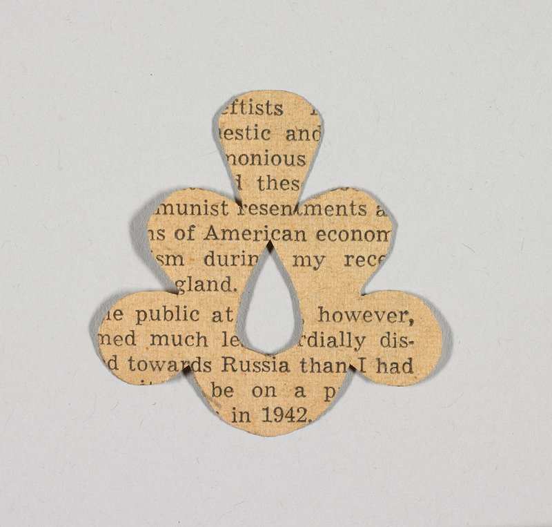 six-lobed flower with teardrop-shaped center cutout; printed newsprint