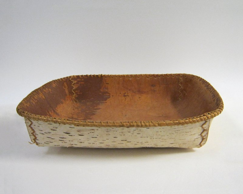 birch bark, rectangular shaped with round sides; wood strip reinforcing top edge; light brown top, tan bottom