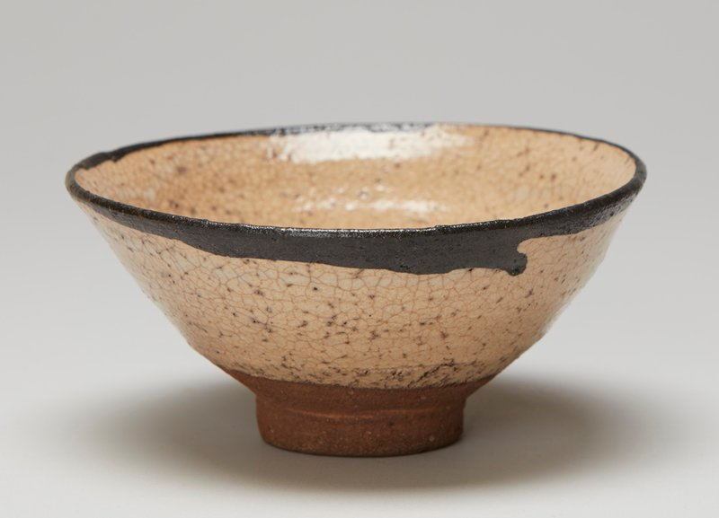 tea bowl; wide, rather tall ring foot; rounded outward-flaring dish shape; tan with brown rim; milky white line at interior and white drips on exterior
