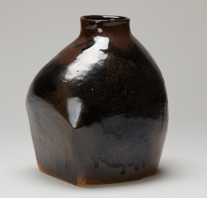 asymmetrical form; flat rectangular base with one rounded corner; organic form with two rather flat side planes; wide sloping shoulder with short neck and wide round mouth; black and brown; white clay