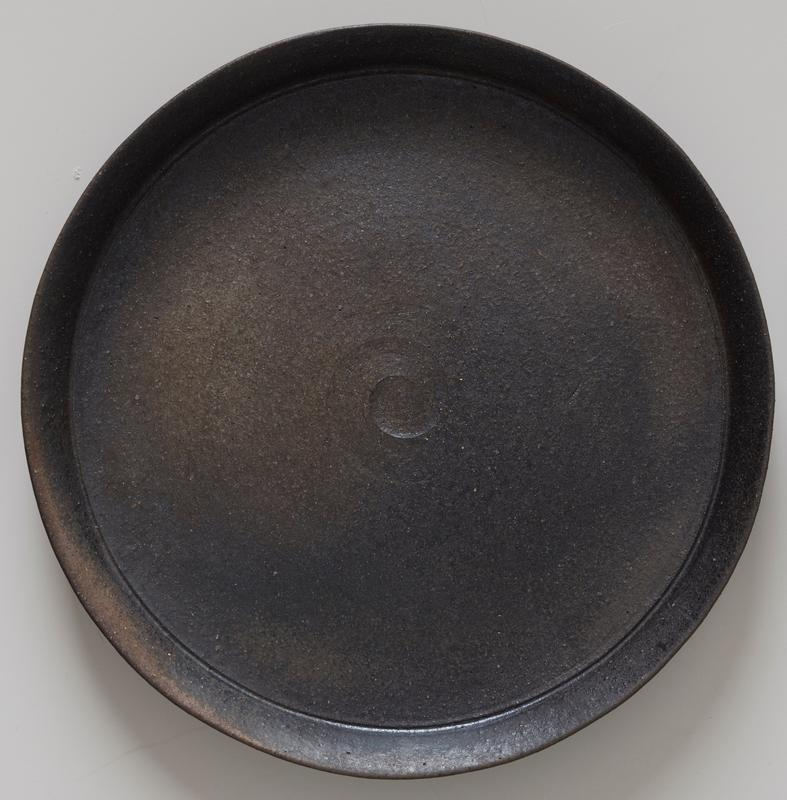 slightly concave bottom; flat plate with articulared, nearly vertical rim; dark grey; small swirl at center