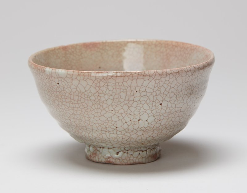 rather tall ring foot; rounded body with tall sides; milky glaze with brown crackles and pink and light blue undertones