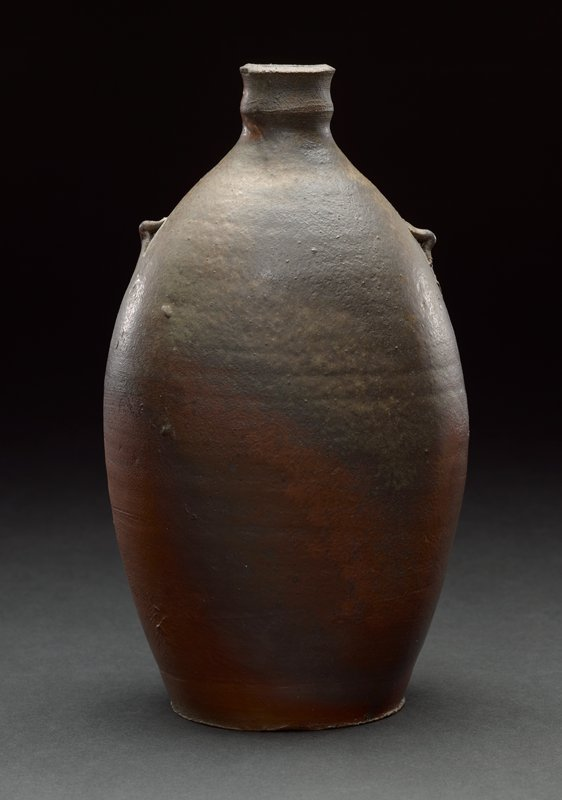 """flat base; rounded form, slightly flattened on two sides; two tiny decorative """"handles""""; short spout; mottled dark reds, brown, tans"""