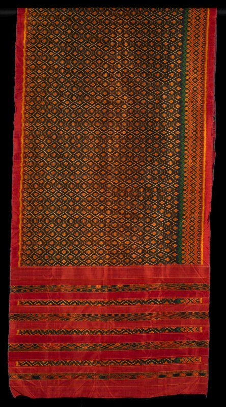 seven bands of geometric designs at either end; central panel floral motif on black ground with wide geometric panel along one selvedge edge; colors--red with gold, black and green