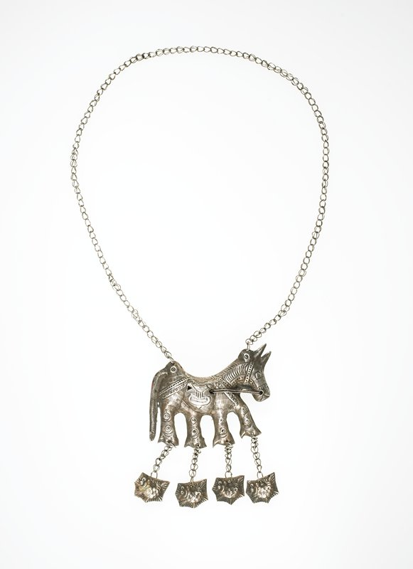 necklace with long, thin chain; hollow horse on chain; four fish dangling down from the horse's four legs; horse has a saddle on and reins in its mouth; circle designs on horse's legs