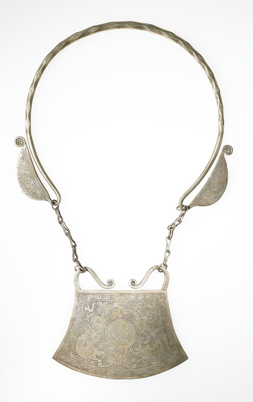 pendant necklace; neck ring has diamond-shaped texture ending in large, flat hooks with incised wave designs; pendant, attached by five-link chain, is flat with two dragon motifs and a circular central motif with two outer fish and two inner fish; key design around outer edge