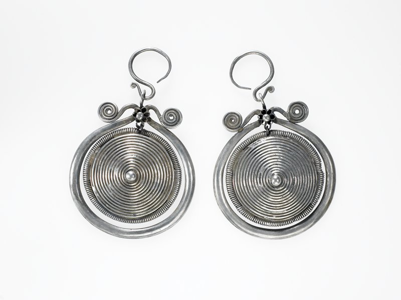 pair of earrings, each earring made from a wrapped wire cone; cone has border of coiled wire; cone is suspended from a thick loop of wire that borders it; loop ends in curlicues and has a flower decorating the connection between the curlicues; ear piece is S-shaped wire