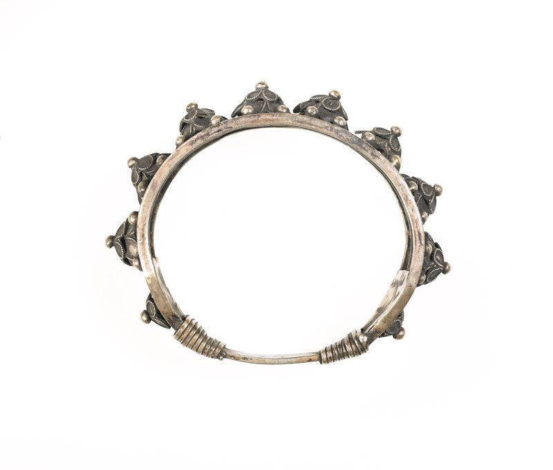 one of a pair of bracelets; bracelet has one row of relief flowers running around the middle; border of filigree and a thin rim of silver runs along the edges; ends have a triangular platform with one flower in it; connecting piece narrows and has thin square wrapped on each side