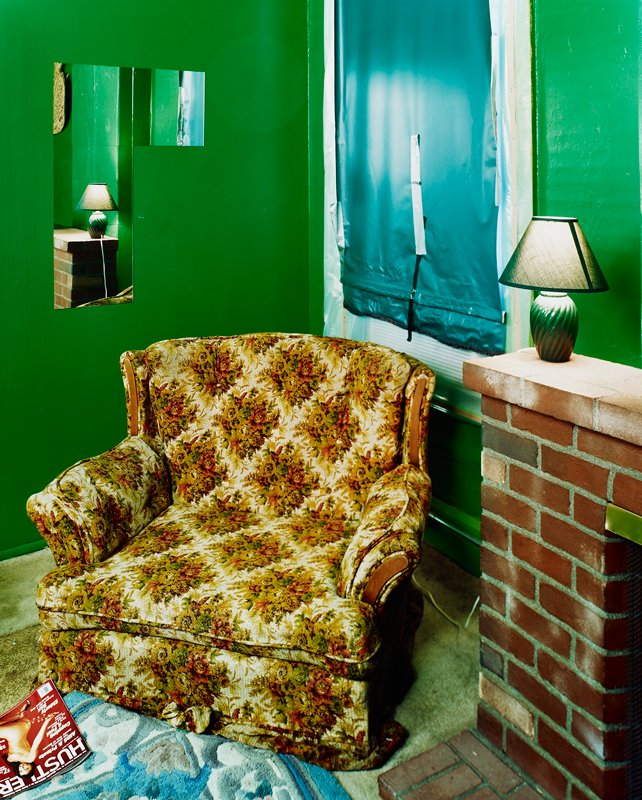"wing chair with flowered upholstery; fireplace at right with lamp; green walls; duct taped green window shade; ""Huster"" magazine on floor next to chair; photographs of fireplace and lamp taped on wall in ULC"