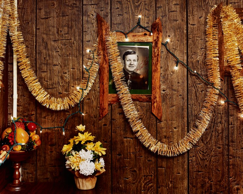 wood paneling on wall; Christmas garland and lights; black and white signed photo of man; artificial fruit and flowers, LLC