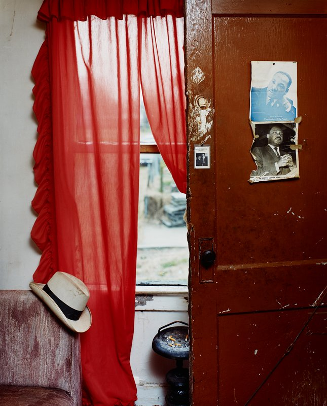 brown door at right with three pictures of Martin Luther King, Jr.; red curtains; white hat on chair; floor stand ashtray