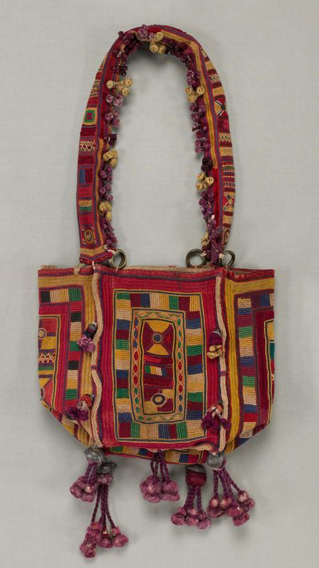 rectangular, squared-off shape; strap attached to bag with metal rings; body of bag and strap stitched overall with geometric designs-predominantly squares and rectangles and predominately in red and maroon; purple and yellow tassel clusters on strap; longer purple tassels on bottom corners and bottom center, embellished with metal elements; bell on long white and red twisted cord on one side