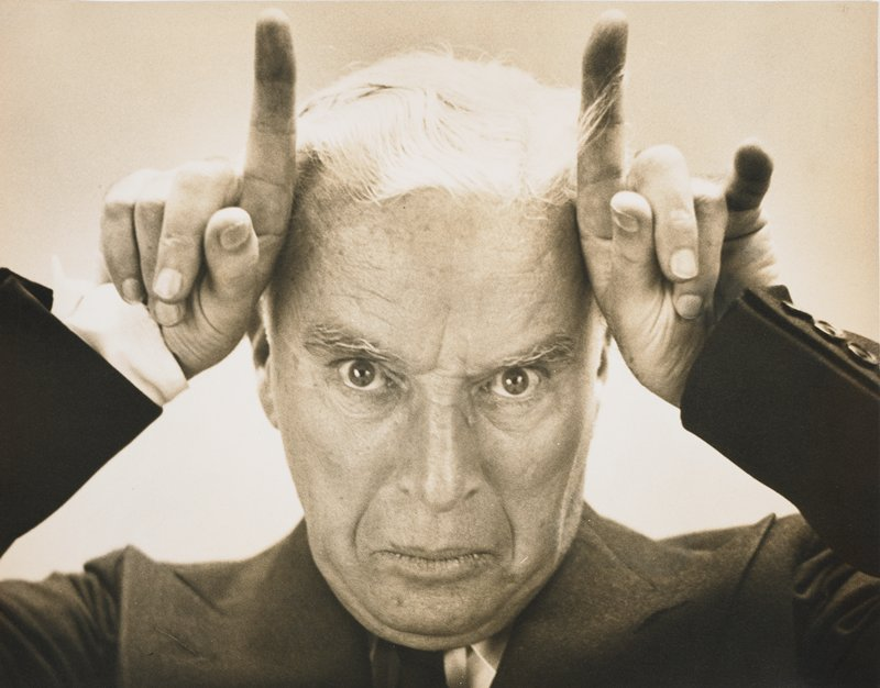 portrait of elderly Charles Chaplin, wearing a suit, with his hands held up to his temples, index fingers pointing upward, in the manner of horns