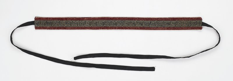black backing and ties; embroidered on top with swastika-key design in brown bordered with maroon on off-white fabric