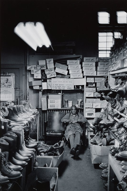 man seated at end of aisle of racks of shoes, looking at camera