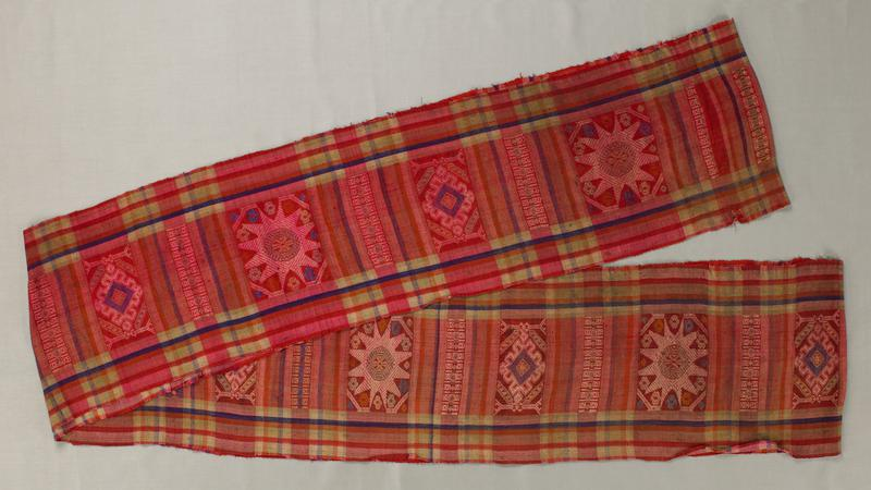 long tube of plaid fabric in shades of red and blue; embroidery: geometric star in octagon and diamonds in rectangle alternate with stripes of squares, three squares wide; embroidery colors include blue, green and pink