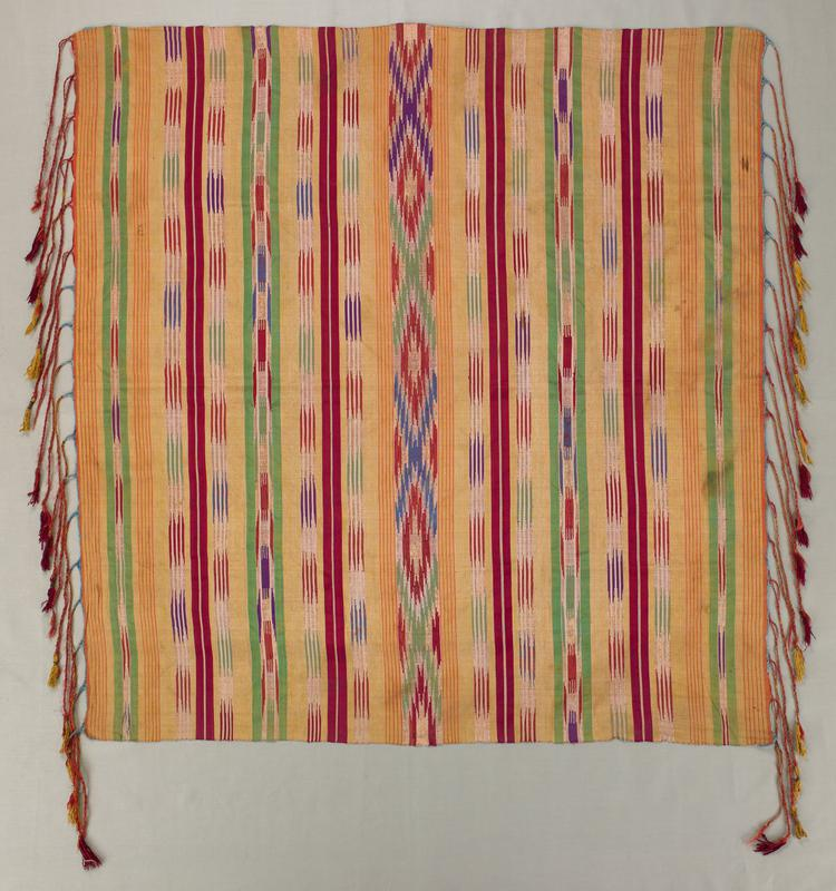 striped and ikat-like bands in orange, yellow, green, white, red, purple and blue; blue stitched edging on two sides; red and yellow tassels on braids on two sides