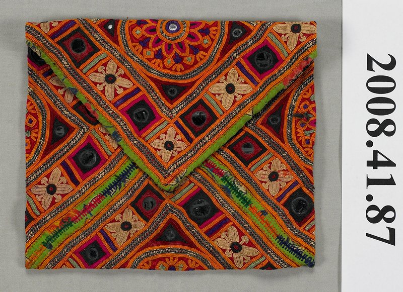 small bag embroidered with mirrors; circles, squares and floral motifs; colors include orange, magenta, purple, green, rust and yellow; edges bound with printed fabric in similar colors