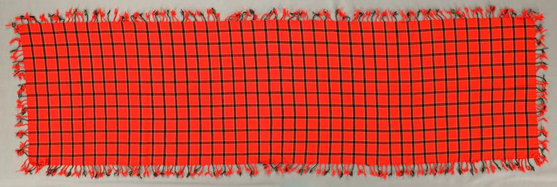 bright red-orange with plaid design in white, green and black; twisted fringe on all four sides