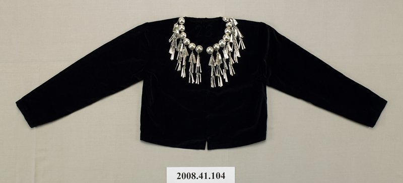 short; black velvet; snap front; large metal studs around neckline; all studs except one have pendants hanging from chains: bugle shapes and flat feather-like shapes